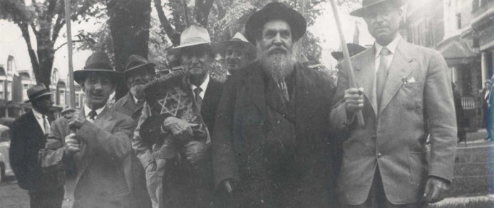 The Strettiner Rebbe of Toronto marching down Brunswick Avenue at a dedication of a sefer Torah in the 1940s
